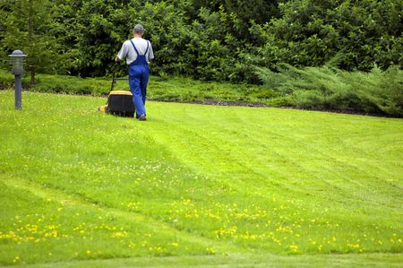 outside machines: Gardener mowing. A lot of copyspace at the bottom.