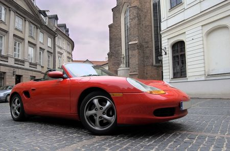 Red sport car in the old town scenery Editorial