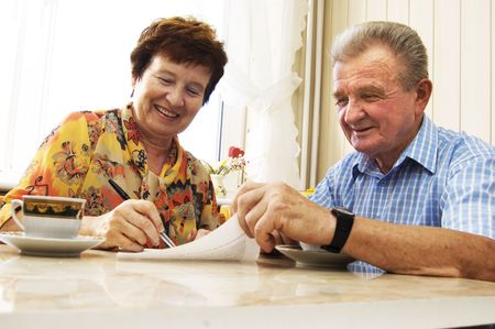 Senior couple signing document in home Stock Photo - 3581443