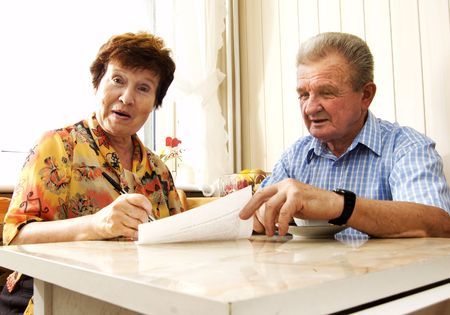 Senior couple signing document in home. Surprised woman Stock Photo - 3581434