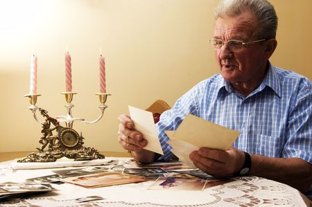 reminisce: Senior man looking at old photographs. Reminisce about the past Stock Photo