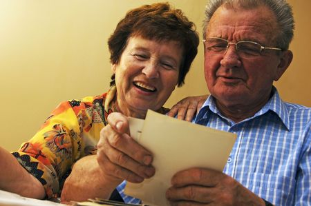 Senior couple looking at old photographs. Reminisce about the past