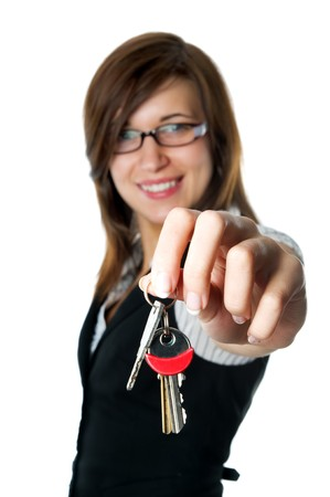 Smiling developer gives keys to new home. Isolated on white background Stock Photo