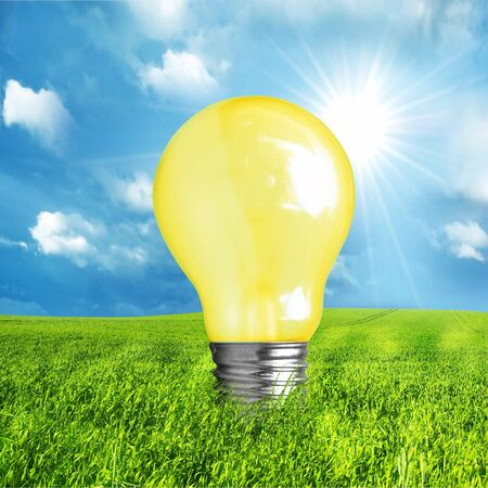 Green energy concept. Light bulb on nature background photo