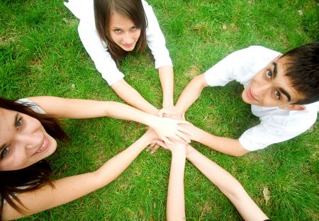 Group of friends joining hands. Unity, teamwork concept photo