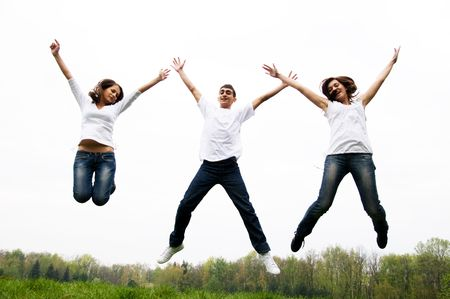 Three happy friends jumping with hands up photo