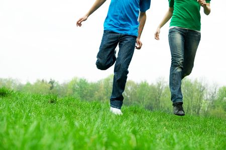 Carefree friends running together on green meadow photo