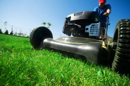 gras maaien: Man maait het gazon. Tuinieren