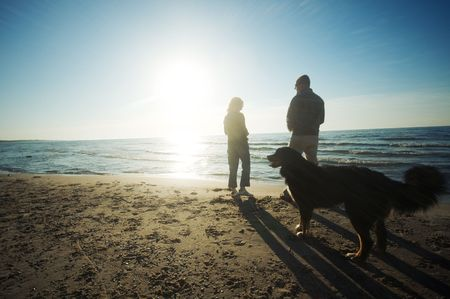 Happy couple with dog on the beach photo