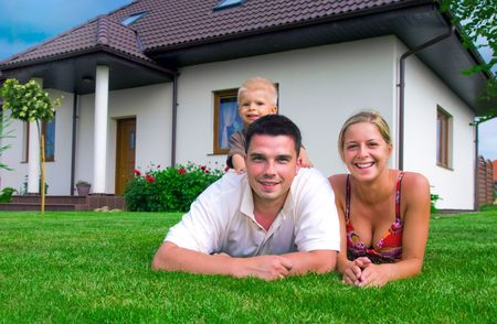 lying in front: Happy family in front of their house Stock Photo