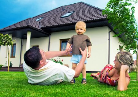 home insurance: Happy family in front of their house Stock Photo