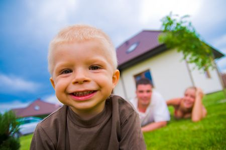 lying in front: Happy child in front of the house with parents in the background