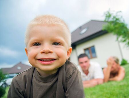 new generation: Happy child in front of the house with parents in the background