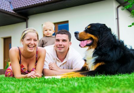 animal family: Happy family in front of their house Stock Photo