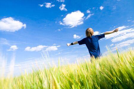 Gelukkig mens met armen omhoog op zomer veld