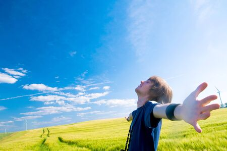 Happy man with arms up on summer lanscape photo