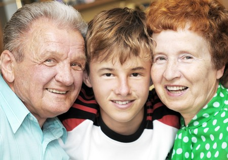 Grandparents with grandson embracing together portrait photo