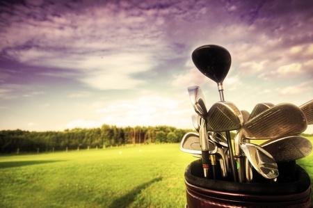 golfing: Professionele golf gear op het golf veld bij zons ondergang. Stockfoto