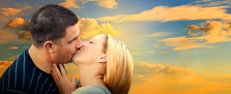 Couple kissing in romantic love scenery on sunset sky. Panorama version photo