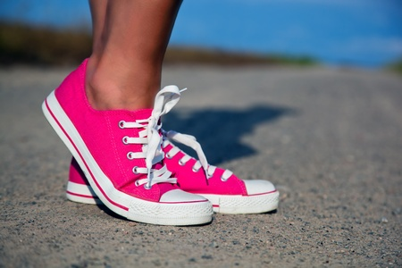 young girl feet: Pink sneakers on girl, young woman legs, outdoors
