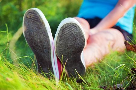 Pink sneakers on girl legs on grass during sunny summer day. photo