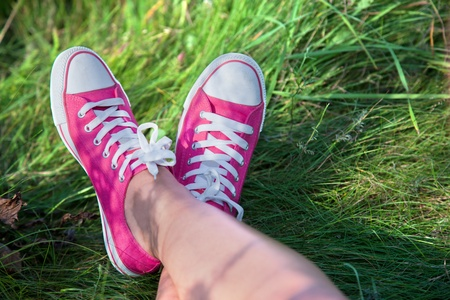 Pink sneakers on girl legs on grass during sunny summer day. Stock Photo - 10859169