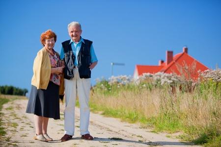 Feliz pareja senior en frente de su casa