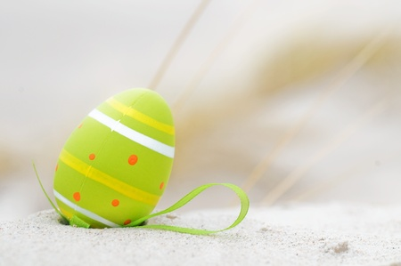 Easter decorated egg on sand. Beach in the background photo