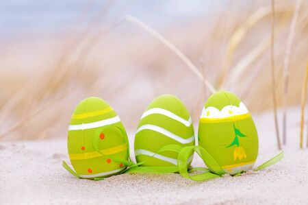 Easter decorated eggs on sand. Beach and ocean in the background