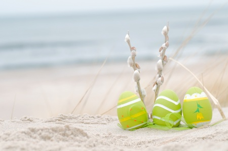 Easter decorated eggs and catkin on sand. Beach and ocean in the background Stock Photo