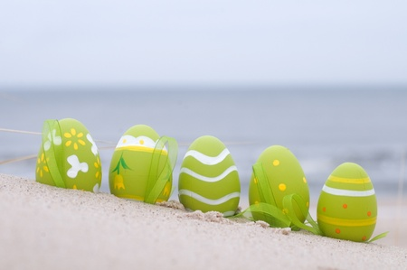 april: Easter decorated eggs on sand. Beach and ocean in the background Stock Photo