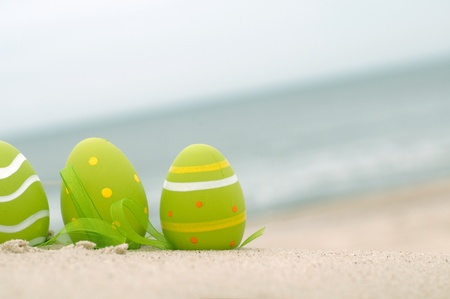 Easter decorated eggs on sand. Beach and ocean in the background Stock Photo
