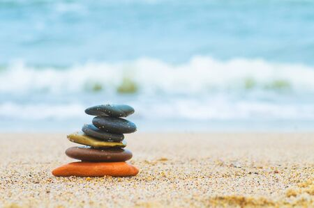 Stack of beach stones on sand. Ocean in the background photo