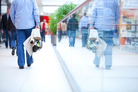 Die Menschen in Eile in einem modernen Einkaufszentrum. Close up und Reflexion eines Mannes, der