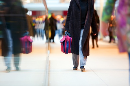 malls: People in rush in a modern shopping mall. Close up and reflection of a woman walking Stock Photo