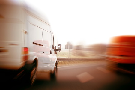 Transportation, logistics concept. Delivery vans, trucks on a freeway, speed motion blur.