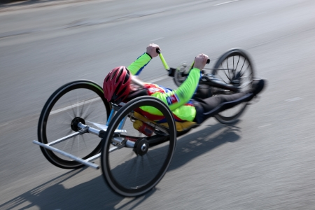 people with disabilities: Wheelchair marathon compatition. Disabled man speeds moving fast. Lens motion blur