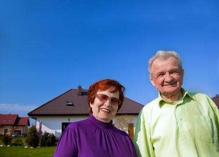 Senior smiling couple in front of their new house photo