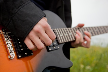 Close up of a man playing guitar outdoors photo
