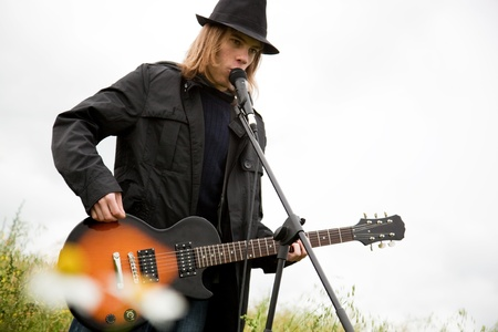 bass player: Man in hat playing guitar outdoors. Stock Photo