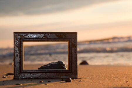 recollection: Frame on the beach at sunset. Conceptual, memories from holidays. Stock Photo