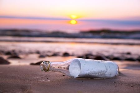 Bericht in de fles op het strand bij zonsondergang
