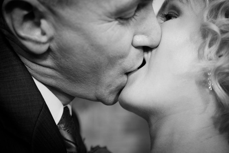 romantic kiss: Happy bride and groom kissing. Black and white