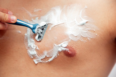 Young man shaving his chest, torso using a gel and a razor Stock Photo - 11696836