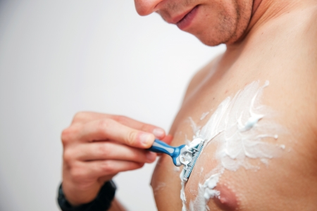 Young man shaving his chest, torso using a gel and a razor photo