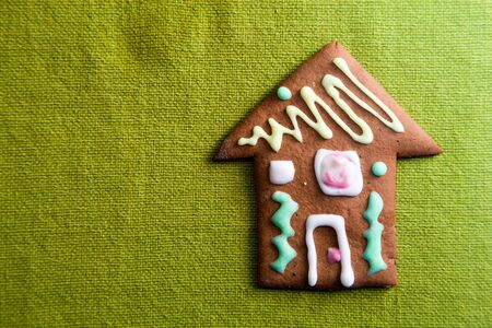 real estate investment: Small cookie house on green background
