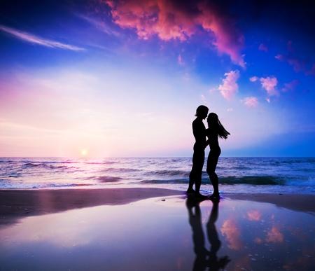 """Romantyczna para o caÅ'ować siÄ™ na plaży o zachodzie sÅ'oÅ""""ca Zdjęcie Seryjne"""