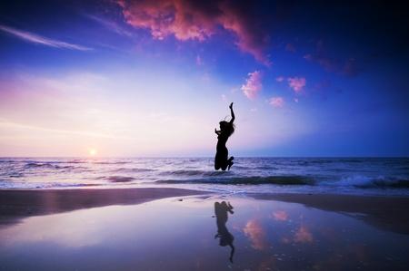 Ragazza salto di gioia sulla spiaggia al tramonto
