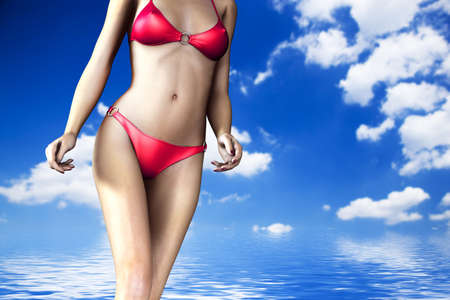 Sexy woman body in bikini on ocean and sky background. photo