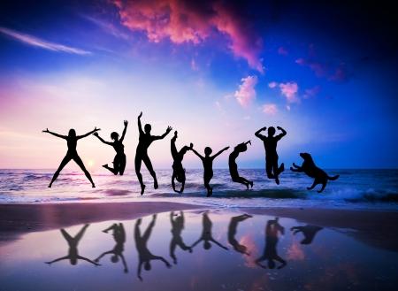 Gelukkige mensen en hond springen samen op de zonsondergang strand